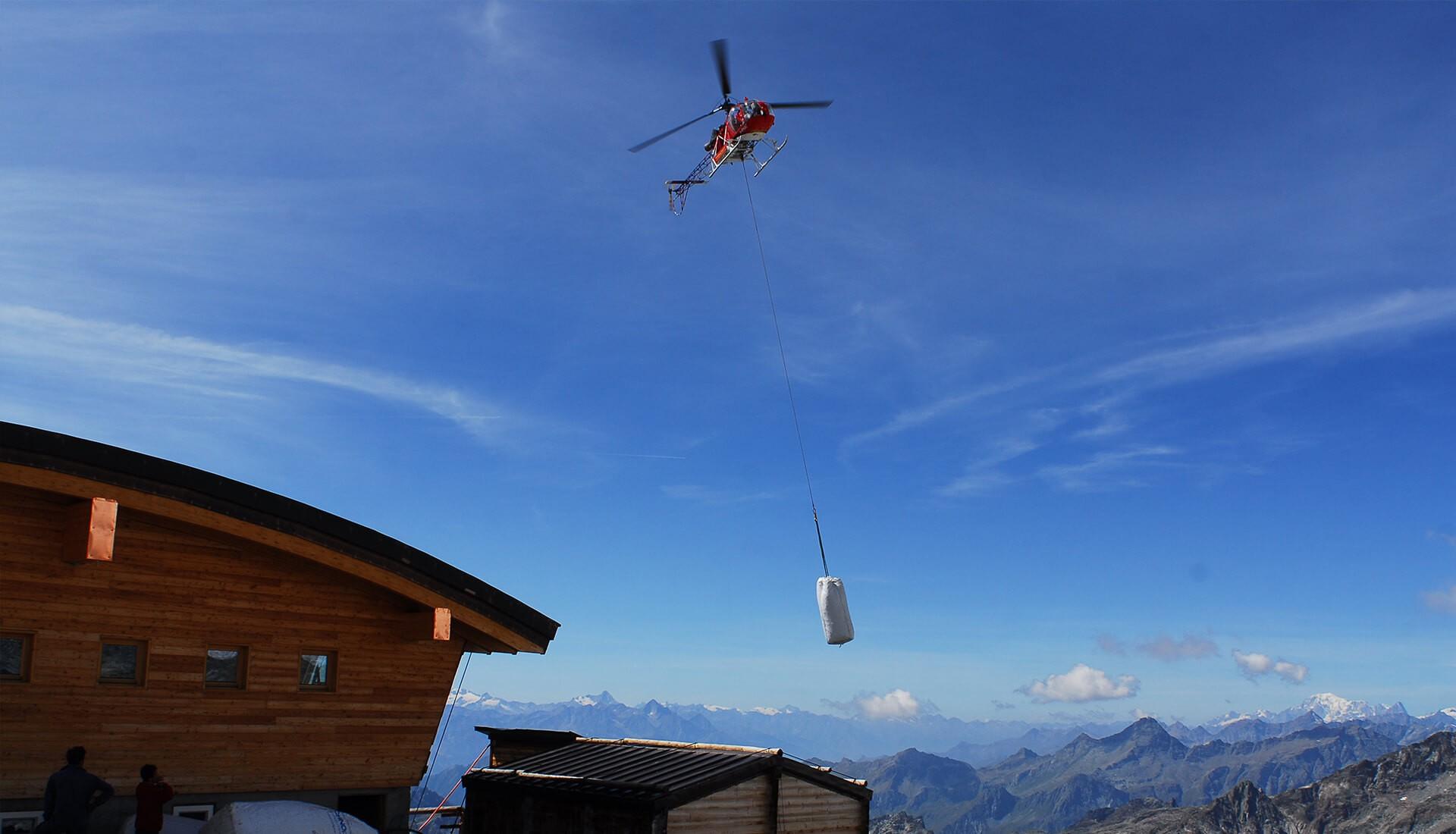 Baustoffe werden mit Helikopter auf Berg transportiert
